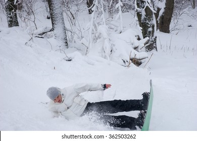 Young man practicing a jump on his snowboard landing on his side in the snow in a flurry of snowflakes