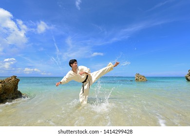 Young man practicing karate at the beach.