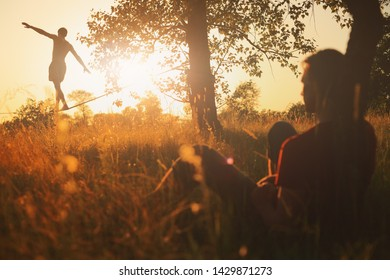 Young man practicing on slackline in the meadow at sunset.