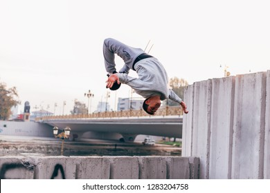 Young man practicing parkour at the city park,doing tricks and jumps.