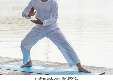 Young man practicing traditional Chinese Tai Chi, boxing, Tai Ji Chuan,   and Qi gong in the park for healthy, traditional chinese martial arts concept.