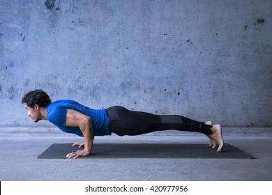 Young man practicing yoga. Basic yoga pose: chaturanga dandasana.