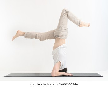 Young man practicing yoga by doing head stand at home on yogi mat.