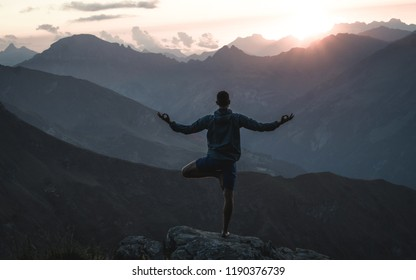 Young man practicing yoga. He is stretching and feels relaxed at sunset in the Swiss Alps at glacial teal lake on the Pizol 5-lakes hike
