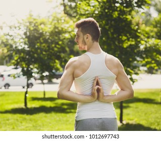 Young man practicing yoga, making asana exercises, looking away. Guy do Reverse Prayer Pose, back and shoulders stretching. Healthy lifestyle in fitness club.
