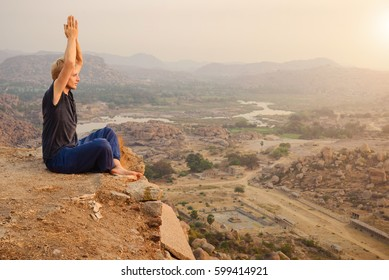 Young man practicing yoga at mountain cliff on sunrise in Hampi, India