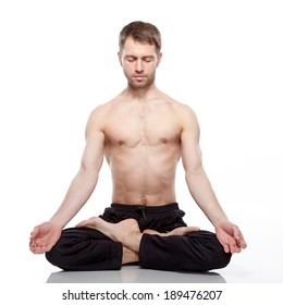 young man practicing yoga on white background, meditating in lotus position.