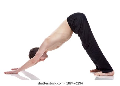 young man practicing yoga on white background, standing in the Downward Facing Dog position.