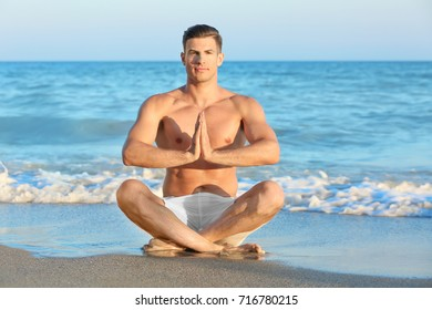 Young man practicing yoga on sea beach
