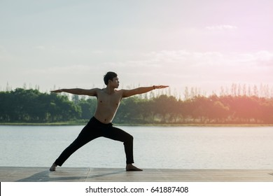 Young man is practicing yoga at river.man yoga - relax in nature