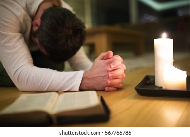 Young man praying, kneeling, Bible and candle next to him.