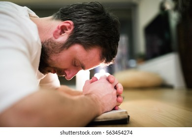 Young man praying, kneeling on the floor, hands on Bible