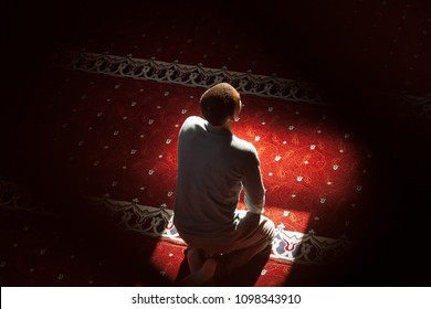 young man praying in the mosque