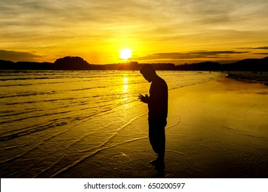 young man praying on the beach with  golden sunset