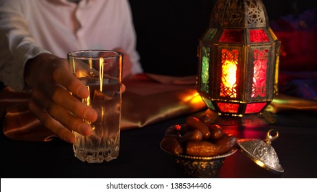 A young man prays and drinks water. Evening meal during the Holy Muslim month of Ramadan