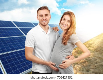 Young man with pregnant wife and solar panels on background