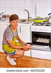 Young man prepares cookies in oven.