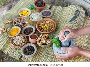A young man preparing ayurvedic medicine in the traditional manner.
