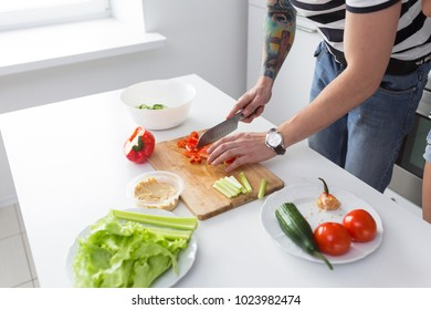 Young man preparing delicious and healthy food with vegetables in the home white kitchen