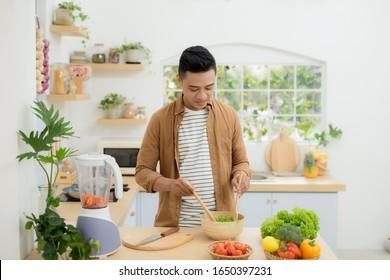 Young man preparing healthy vegetable salad