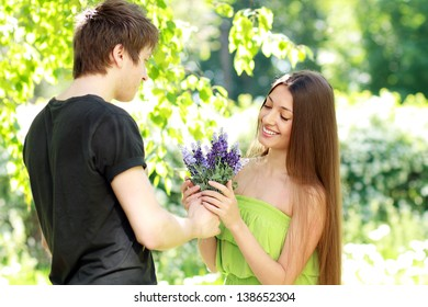 A young man presenting blue flowers to a woman on a summer day
