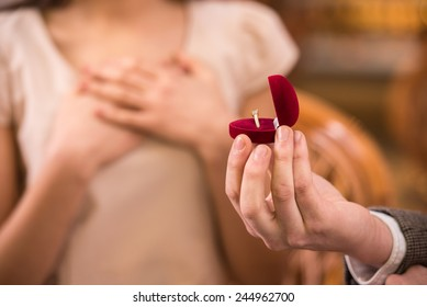 Young man is presenting engagement ring to his girlfriend.