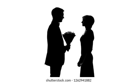 Young man presenting girlfriend flower bouquet, birthday celebration, first date
