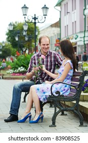 Young man presenting a rose to a beautiful woman sitting street bench wile dating