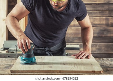 Young Man  processes the board with a random orbit sander in the workshop