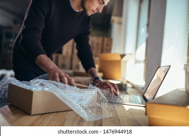 Young man with a product looking at laptop. Entrepreneur verifying the shipment details before delivering to customer.