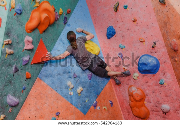 Young man professional climber exercising at indoor bouldering artificial wall
