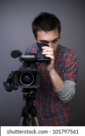 Young man with professional video camcorder on gray background