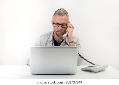 young man programmer with black glasses working with his laptop while speaking at phone. studio portrait on white background