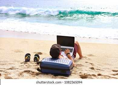 Young man, programmer on sandy beach leaning on suitcase, coding on a blank screen laptop computer, typing, blogging. Freelance, distance work concept. Sea view, ocean waves. Background, copy space