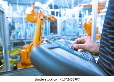 Young man programming industrial automatic robot in the automotive industry, industrial concept