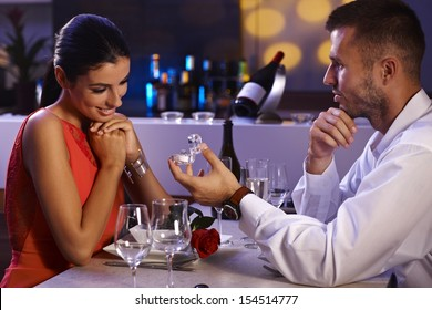 Young man proposing to beautiful woman, holding engagement ring, waiting for answer.