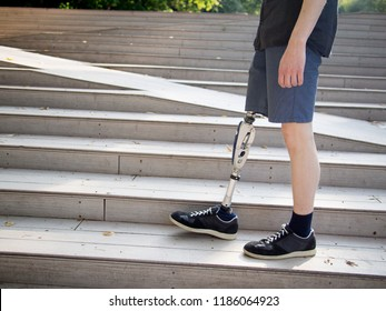 Young man with prosthetic leg walking outdoors along the stairs