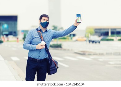 Young man with protective face mask using mobile phone app waiting for rideshare – Casual business man with hand up calling taxi hailing from sidewalk – Passenger using online map to call cab