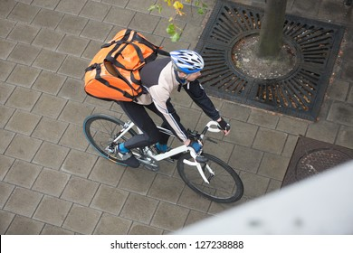 Young man in protective gear with backpack riding bicycle on sidewalk