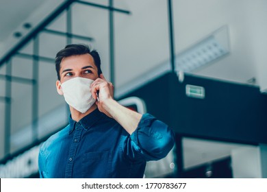 young man in a protective mask is choosing a contact in his smartphone