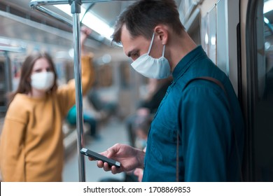 young man in a protective mask looking at the screen of his smartphone