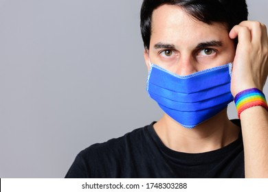 Young man with protective mask and rainbow flag wristbands.Portrait of a gay man looking at the camerawith face mask against coronavirus. LGTB. COVID-19