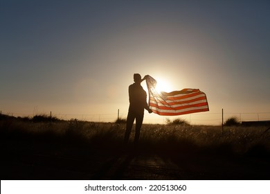 Young man proudly waving the American flag at sunset