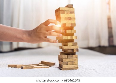 Young man pulling out wood block fail on building tower at home and drape change, choice business risking dangerous project plan failure construction concept.