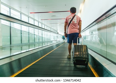 Young man pulling suitcase in modern airport terminal. Travelling guy wearing sportware  walking away with his luggage while waiting for transport. Rear view. Copy space