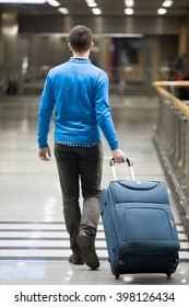Young man pulling suitcase in modern airport terminal. Travelling guy wearing smart casual style clothes walking away with his luggage while waiting for transport. Rear view. Vertical image