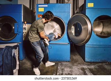 Young man pulls out his girlfriend from a large industrial washing machine, funny couple moments