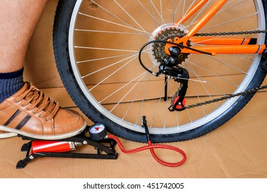 The young man pumping air into the bicycle' s wheel