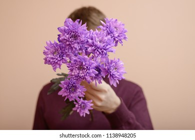 Young man with purple flowers in his hand.