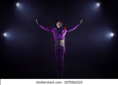 Young man in the purple suit standing on the background of the spotlight. Showman raised hand, show begins